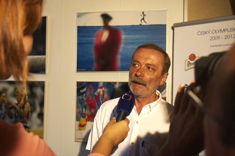Jiří Pekárek v rozhovoru pro ČT, za ním jeho nejoblíbenější fotografie z OH 1992 v Barceloně - poslední maratonec
